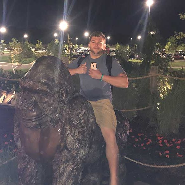 posing with ape statue